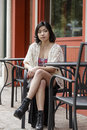 Asian woman in lifestyle locations sitting at a table on the street Royalty Free Stock Photography