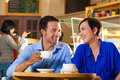 Asian woman and man in an coffee shop friends enjoying her leisure time a cafe drinking or cappuccino talking about some things Royalty Free Stock Photo
