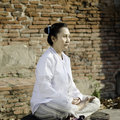 Asian woman meditating in ancient buddhist temple Stock Photo