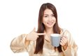 Asian woman in pajamas point to toothbrush in mug Royalty Free Stock Photo