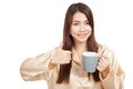 Asian woman in pajamas thumbs up with toothbrush in mug Royalty Free Stock Photo