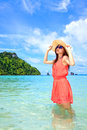 Asian woman in a pink dress standing on the beach Stock Image