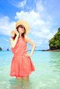 Asian woman in a pink dress standing on the beach Stock Photos
