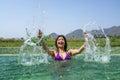Asian woman playing and splashing in the swimming pool purple bikini with mountain green grass field far background Royalty Free Stock Photos