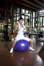 Asian woman posing with swiss ball in a gym Stock Image