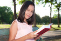 Asian woman reading book in park Royalty Free Stock Images