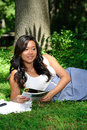 Asian woman reading a magazine in park Royalty Free Stock Photo