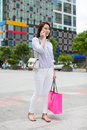 Asian woman shopping bag talking cell phone call Royalty Free Stock Photo