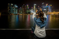 Asian woman sit and take city scape photo by mobile phone Royalty Free Stock Photo