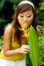 Asian Woman smelling a flower Stock Photo