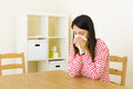 Asian woman sneezing at home Royalty Free Stock Photo