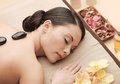 Asian woman in spa with hot stones health and beauty resort and relaxation concept salon getting massage Royalty Free Stock Photo