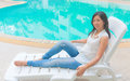 An asian woman standing beside a swimming pool present for relaxation activity in urban life style Royalty Free Stock Photos