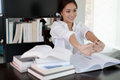 Asian woman stretching after reading book and work hard and smiling in the home office Royalty Free Stock Photo