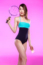 Asian woman in swimsuit holding badminton racquet with shuttlecock and looking away Royalty Free Stock Photo