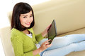 Asian woman with tablet pc beautiful smiling sitting on the couch Royalty Free Stock Photos