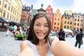 Asian woman taking self portrait selfie stockholm photo on europe travel happy candid tourist on stortorget big square gamla stan Stock Photo