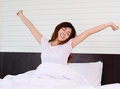 Asian woman teenager wake up and relaxation in bed bedroom Royalty Free Stock Photography