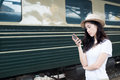 Asian woman texting on smartphone at train station with railway Royalty Free Stock Photo