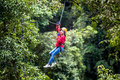 Asian woman TOURIST adult wearing casual clothes Zip Line On Focus FOREST TR Royalty Free Stock Photo