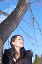 Asian woman beside tree trunk Royalty Free Stock Photos