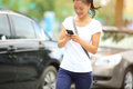 Asian woman use smartphone beside car Stock Photo