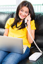 Asian woman using laptop and phone on couch young handsome sitting multitasking by telephoning with Royalty Free Stock Photos