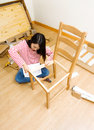 Asian woman using strew driver for chiar assembling at home Stock Photo