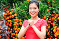 Asian woman wishing a happy chinese new year smiling front of fruitfull cumquat trees Royalty Free Stock Images