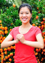 Asian woman wishing a happy chinese new year smiling front of fruitfull cumquat trees Stock Photo