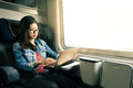 Asian woman work on laptop on train, business travel concept, warm light tone Royalty Free Stock Photo