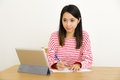 Asian woman writing notes through digital tablet at home Royalty Free Stock Image