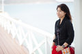 Asian women black jacket woman smiling stood on a bridge made ​​of wood Royalty Free Stock Photo
