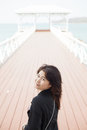 Asian women black jacket woman smiling stood on a bridge made ​​of wood Royalty Free Stock Photos