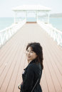 Asian women black jacket woman smiling stood on a bridge made ​​of wood Stock Photo