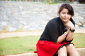 Asian women black shirt sitting on the lawn woman grass in park areas Royalty Free Stock Photos