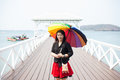Asian women black shirt standing holding an umbrella in the midd woman middle of bridge behind sea and sky during day Royalty Free Stock Images