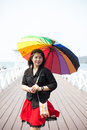 Asian women black shirt standing holding an umbrella woman in the middle of the bridge behind the sea and the sky during the day Stock Image
