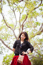 Asian women black shirt standing under a tree woman happy smiling relaxing in the park Stock Photos