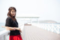 Asian women black shirt standing wooden terrace woman on the of white beach Royalty Free Stock Image