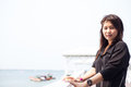 Asian women black shirt standing wooden terrace woman on the of white beach Stock Photography