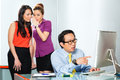 Asian women bullying colleague in office or employee s tattle or whisper about or man him the Royalty Free Stock Photos
