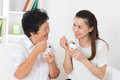 Asian women eating yogurt yoghurt happy family at home beautiful senior mother and adult daughter healthcare concept Royalty Free Stock Photography