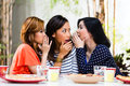 Asian women gossiping about things three indonesian friends gossip and whisper to themselves secrets in tropical environment Royalty Free Stock Image