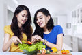 Asian women prepare salad together young in the kitchen Royalty Free Stock Images
