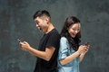 Asian young couple using cellphone, closeup portrait. Royalty Free Stock Photo