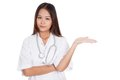 Asian young female doctor show something on her hand isolated white background Royalty Free Stock Photo