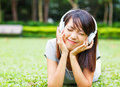 Asian young girl enjoy listen to music on green lawn Stock Photo