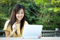 Asian young girl use laptop for search information in the garden Stock Photos