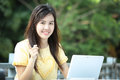 Asian young girl use laptop for search information in the garden Royalty Free Stock Photography
